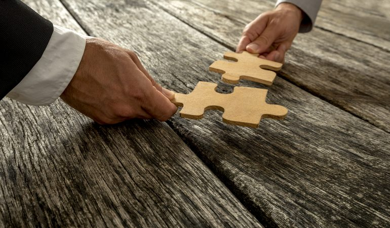 Business partnership or teamwork concept with a business people presenting a matching puzzle piece as they cooperate on finding an answer and solution close up of their hands. ** Note: Shallow depth of field